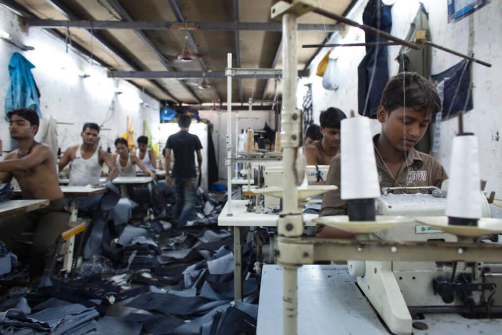 Manufacturing jeans in Dharavi slum, Mumbai, India (Adam Hinton)